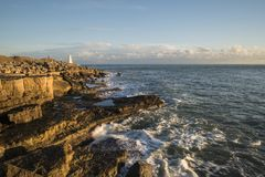 Beautiful vibrant sunset landscape image of Portland Bill rocks Stock Photos