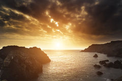 Beautiful sunset landscape over rocky cove looking out to sea Stock Photography