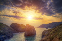 Beautiful sunset landscape over rocky cove looking out to sea Stock Photo
