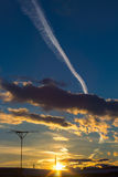 Beautiful sunset with magnificent clouds and the plane trace in blue sky. Stock Images