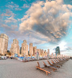 Beautiful sunset on Marina Beach, Dubai with beach chairs and sk Stock Images