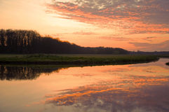 Beautiful sunset in the meadow with a great water reflection. Royalty Free Stock Images