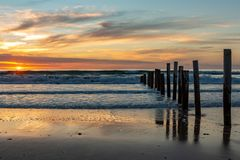 A beautiful sunset at moana beach with the wooden posts seperating the beach in South Australia on 8th November 2018 royalty free stock photography
