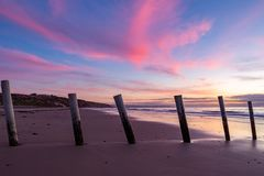 A beautiful sunset at moana beach with the wooden posts seperating the beach in South Australia on 8th November 2018 stock images