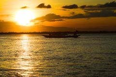 Sunset with boat background photo. A beautiful sunset moments with the black boat sailing on the river water Stock Photos