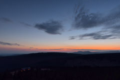 Beautiful sunset in the mountains with illuminated cottage Stock Photography