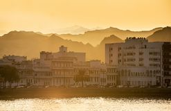 Beautiful sunset in Mutrah in Muscat. Beautiful sunset in Muttrah with mountains and buildings on the background Royalty Free Stock Photography