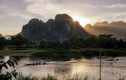 Beautiful sunset on the Nam Song river in Vang Vieng, Laos, crossed by long-tailed boats. Beautiful sunset on the Nam Song river in Vang Vieng, Laos, Asia royalty free stock images