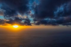 Beautiful sunset at the ocean with fog on the horizon and dark clouds. In the sky stock photography