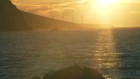 Beautiful sunset on the ocean shore and splashing waves. Romantic sunset by the ocean, on the horizon windmills, waves and splashes stock video footage