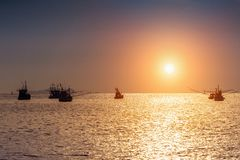 Beautiful sunset at ocean with silhouette of fishing boat.  stock image