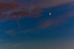 Beautiful sunset with orange clouds, deep blue sky and moon.  Royalty Free Stock Photos