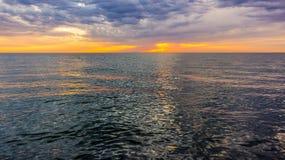 Beautiful sunset over a calm dark sea. Beautiful sunset over the backdrop of a calm dark sea Stock Photos