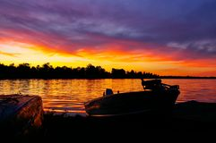Sunset Over Lake With Fishing Boat Docked On Shore. Beautiful sunset over a calm lake as a fishing boat is docked on shore Stock Photography