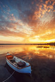 Beautiful sunset over calm lake and a boat with sky reflecting i Royalty Free Stock Images