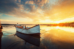 Beautiful sunset over calm lake and a boat with sky reflecting i Royalty Free Stock Image