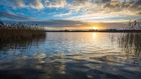 Beautiful sunset over calm lake Stock Photos