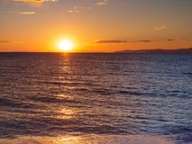 Beautiful sunset over calm seas and empty beach - small islands in the background stock photo