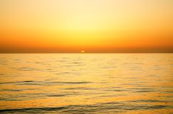 Beautiful sunset over the calm surface of the sea. Sunset on the sea. The sun sets over the sea horizon Stock Images