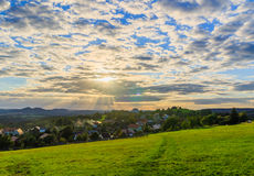 Beautiful sunset over countryside landscape of rolling hills with sun beams piercing sky and lighting hillside Stock Photo