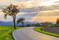 Beautiful sunset over countryside landscape of rolling hills with sun beams piercing sky and lighting hillside Stock Images
