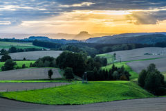 Beautiful sunset over countryside landscape of rolling hills with sun beams piercing sky and lighting hillside Royalty Free Stock Image