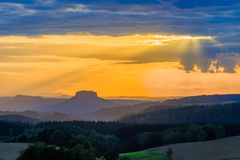 Beautiful sunset over countryside landscape of rolling hills with sun beams piercing sky and lighting hillside Royalty Free Stock Photography
