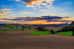 Beautiful sunset over countryside landscape of rolling hills with sun beams piercing sky and lighting hillside Royalty Free Stock Photos