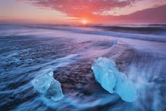 Beautiful sunset over famous Diamond beach, Iceland. This sand lava beach is full of many giant ice gems, placed near glacier. royalty free stock photos