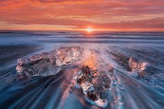 Beautiful sunset over famous Diamond beach, Iceland. This sand lava beach is full of many giant ice gems, placed near glacier. royalty free stock image