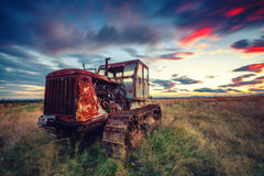 Beautiful sunset over field and old rusty tractor Royalty Free Stock Photography