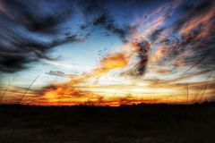 The sky is on fire. Beautiful sunset over a field with Royalty Free Stock Photo