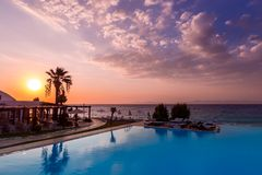 Beautiful sunset over an infinit pool and the Mediteraneean Sea in the Ixia gulf, on the western coast of the Rhodos island, near. The Rhodos city royalty free stock photo