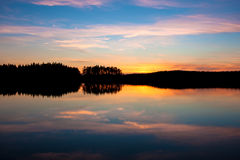 Beautiful sunset over the lake. Colorful sunset over the calm lake in Finland Royalty Free Stock Photos