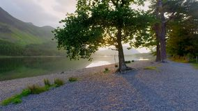 Beautiful sunset over the lake in the Lake District with sunbeam through the tree, England. Beautiful sunset over the lake in the Lake District with sunbeam stock video