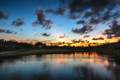 Beautiful sunset over the lake near the golf course in a tropica Royalty Free Stock Image