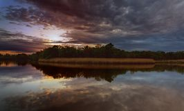 Beautiful sunset over lake with reflection in water, majestic clouds in the sky Toned Image Stock Photo