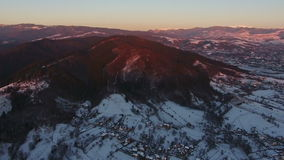 Beautiful sunset over mountain village in winter, aerial view 4 stock video footage