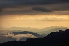 Beautiful sunset over mountains with storm clouds in background. Royalty Free Stock Image