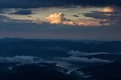 Beautiful sunset over mountains with storm clouds in background. Royalty Free Stock Images