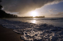 Beautiful Sunset over the ocean with waves moving across the san Royalty Free Stock Image