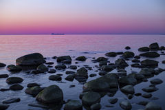 Beautiful sunset over a rocky coast with an oil tanker on the horizon Royalty Free Stock Photos