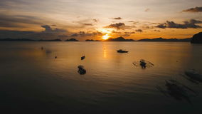 Beautiful sunset over sea, aerial view. Marine tropical sunset over the sea. Aerial view: Sunset over the sea in the background boats, orange sky and islands stock footage