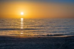 Beautiful sunset over the sea with clear sky in Anna Maria Island, Florida. A very romantic shoreside sunset with orange and blue cloudy sky in Anna Maria Key royalty free stock photo