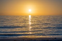 Beautiful sunset over the sea with clear sky in Anna Maria Island, Florida. A very romantic shoreside sunset with orange and blue cloudy sky in Anna Maria Key stock image