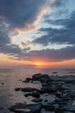 Beautiful sunset over the sea. Rocky shore. Sunset on the beach. Evening. Stones Stock Photography