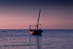 Beautiful sunset over the sea. A small fishing boat. Stock Photos