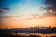 Beautiful sunset over silhouette city skyline and river Stock Image