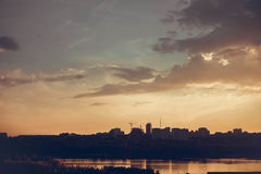 Beautiful sunset over silhouette city skyline and river Stock Images