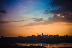 Beautiful sunset over silhouette city skyline and river Royalty Free Stock Images